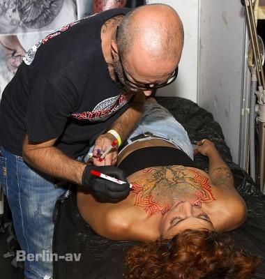 Tattoo Convention Berlin - Tattookünstler zeichnet seinen Entwurf auf das Dekollete einer Kundin.